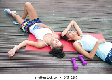 Two happy fit young women friends lying down tired after workout exercising in a park. Active healthy lifestyle concept