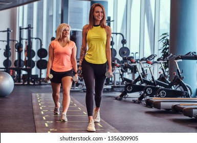 Two happy fitness girls in sportswear doing lunges with dumbbells in the modern gym. Health, diet, sport