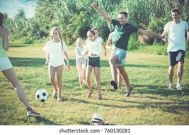 Two happy french friendly families with children playing football in nature at summer