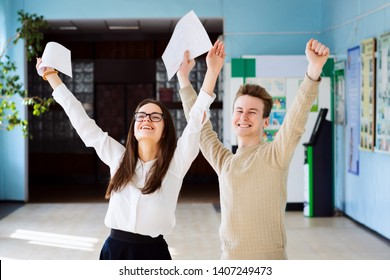 Two happy friends happy after researching their checked exams, raising hands up and expressing amusement of getting excellent grades for their work