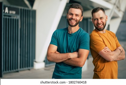 Two happy friends or brothers in colorful t-shirts are standing back to back with crossed arms outdoors