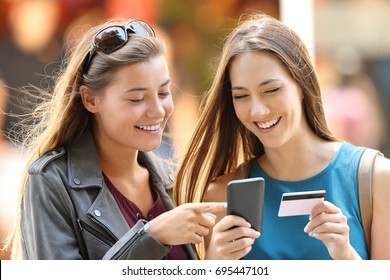 Two happy friends buying on line with credit card and smart phone on the street