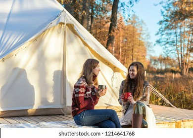 Two happy friends drinking coffee while relaxing near canvas bell tent in the morning in a forest