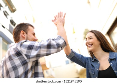 Two happy friends giving high five standing in a city street