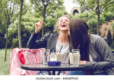 Two happy friends laughing with coffee