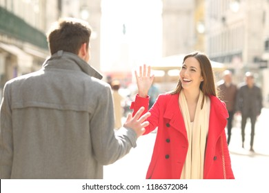 Two happy friends meeting and greeting in the street of a big city
