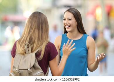 Two happy friends meeting and greeting on the street with a blurred background
