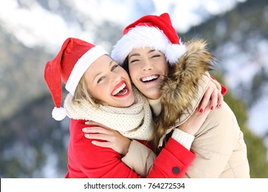 Two happy friends on christmas holidays looking at you with a snowy mountain in the background