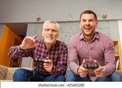 Two happy friends playing video games at home