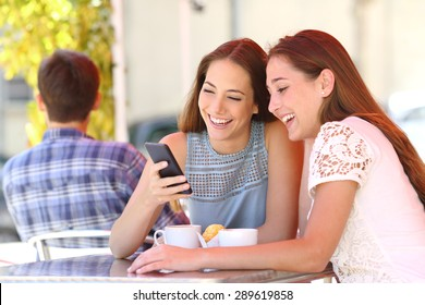 Two happy friends or sisters sharing a smart phone in a coffee shop terrace looking at device in summer
