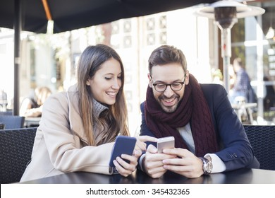 Two happy friends with smart phones in a coffee shop terrace looking at device