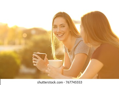 Two happy friends talking outside in a house balcony at sunset