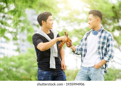 Two happy friends toasting with bottles of beer during their walk outdoors