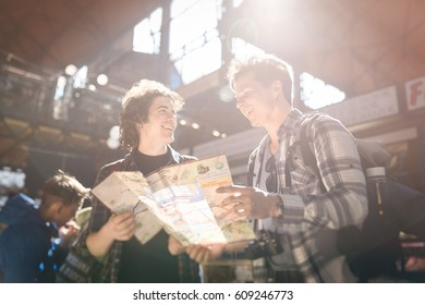 two happy friends traveling, checking the map in a big market, with a beautiful sun light on the background
