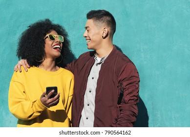 Zwei glückliche Freunde, die das Handy auf der Straße benutzen. Freundschaftskonzept.