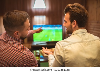 The two happy friends watch a football