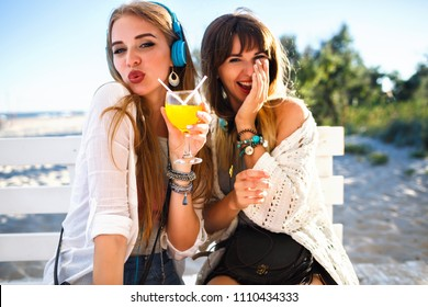 Two happy funny hipster girls having fun on beach summer party, laughing and sensing kiss, drinking tasty cocktail, bright summer outfits and accessories, listening music at headphones.
