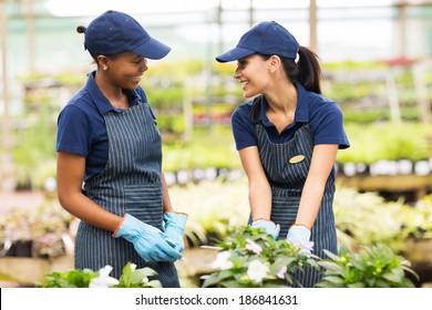 two happy gardeners talking in greenhouse