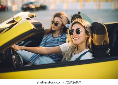 Two happy girl friends taking selfie when road trip in convertible car. Cheerful students having fun when travel in California.