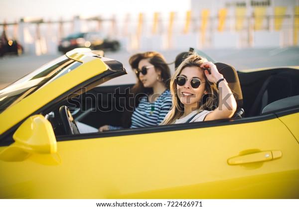 Zwei glückliche Mädchen Freunde, die sich selbst nehmen, wenn Straße Reise in Cabrio Auto. Fröhliche Schüler, die Spaß haben, wenn sie in Kalifornien reisen.