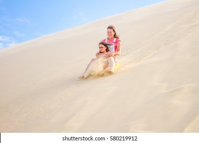 two happy girl sliding a board on sand dunes