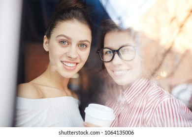 Two happy girlfriends or groupmates looking at camera through cafe window during coffee-break