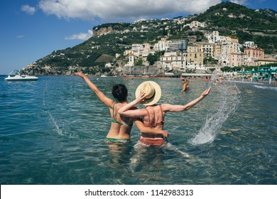 Two happy girlfriends making fun on the coast of tropical sea