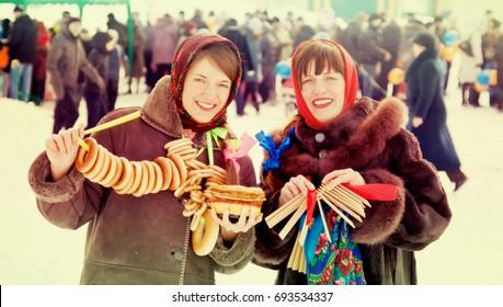 Two happy girls celebrating  Pancake Week at Russia