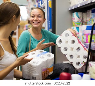 Two happy girls choose toilet paper in the shop