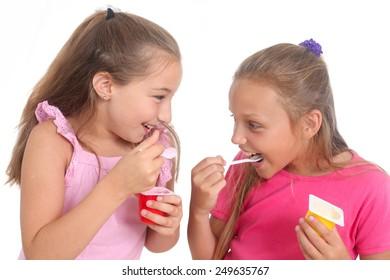 two happy girls eating yogurt