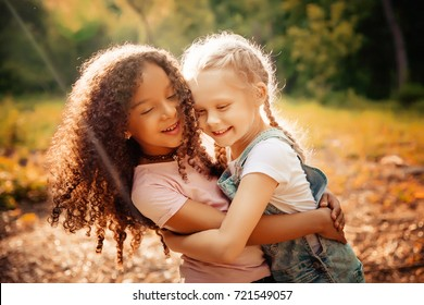 Two happy girls as friends hug each other in cheerful way. Little girlfriends in park. Children Friendship Together Smiling Happiness Concept