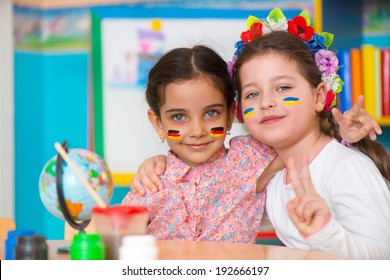 Two happy girls in international summer camp with flags on cheeks
