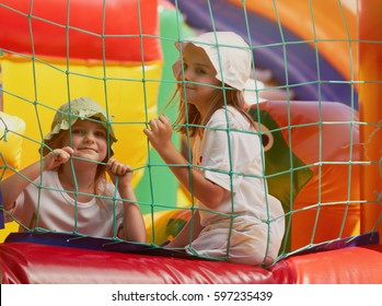Two happy girls play in bounce house.Kids plays in bouncing inflatable castle outdoor.Happy small girls,children playing in bouncy castle playground outside in summer day