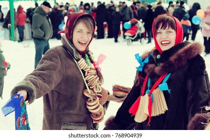 Two happy girls plays during Shrovetide at Russia