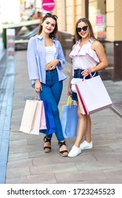 Two happy girls posing on the street after shopping, carrying bags in their hands, delighted and satisfied.