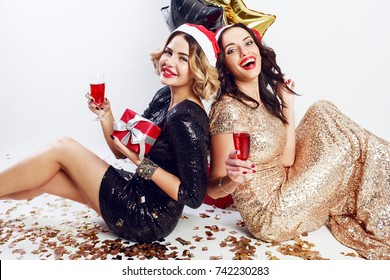 Two happy   girls   in  in red christmas santa claus holiday hat sitting on floor , drinking wine , laughing, enjoying time together.   Wearing  sparkly  black and golden  evening  dress.