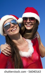 Two happy girls in Santa Clause suit having fun on the beach