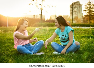 Two happy girls sit on the grass in the backlight and laugh