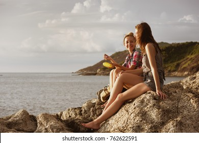 Two happy girls are sitting on sea backdrop and speaking at sunset beach