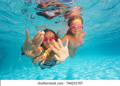 Two happy girls swimming under clear water of pool
