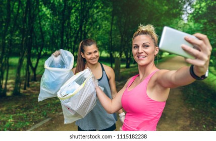 Two happy girls taking a selfie showing trash bags after plogging