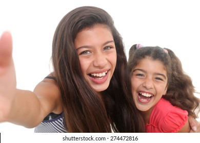 two happy girls taking a selfie on a white background