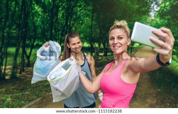 Zwei fröhliche Mädchen, die nach dem Holzeinschlag Müllsäcke aus dem Selfie nehmen