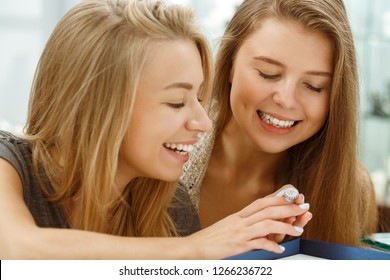 Two happy girls trying on wonderful big ring with precious stones in jewelry store. Pretty clients smiling, looking and at it and talking together. Concept of consumerism and accessories.