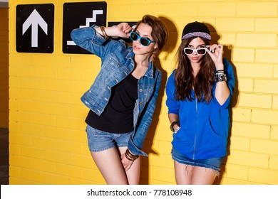 Two happy girls wearing stylish bright outfits, denim shorts and sunglasses going crazy and having great time. Standing together near yellow brick wall enjoying day off and looking to the camera.