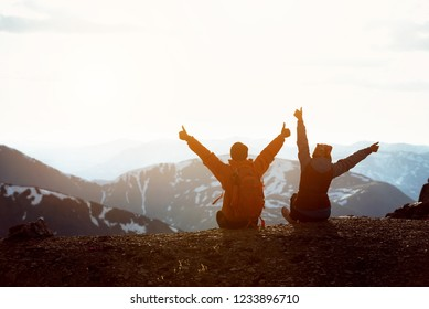 Two happy hikers sits on mountain top with raised arms and having fun