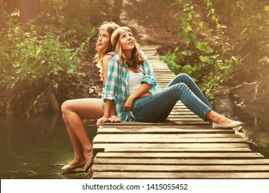 Two happy hipster teen girls sitting on wooden bridge in summer forest