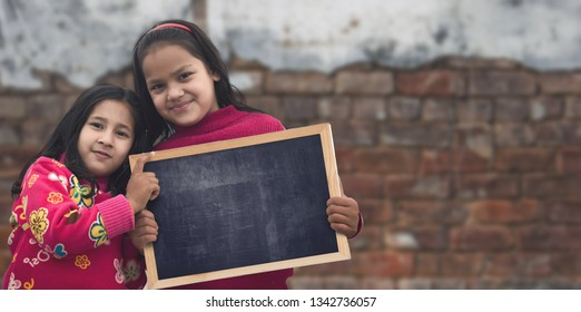 Two Happy Indian Little girl standing holding chalkboard (slate) looking directly at camera. selective focus.