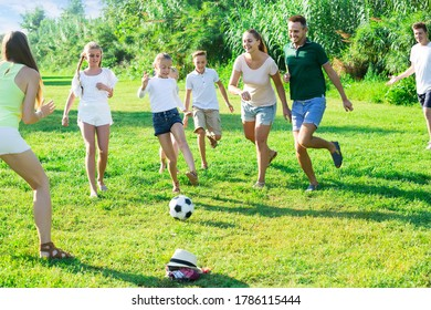 Two happy italian  friendly families with children playing football in nature at summer