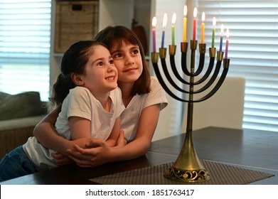 Two happy Jewish sisters looking at a beautiful menorah candelabra glowing on the eight day of Hanukkah Jewish holiday.